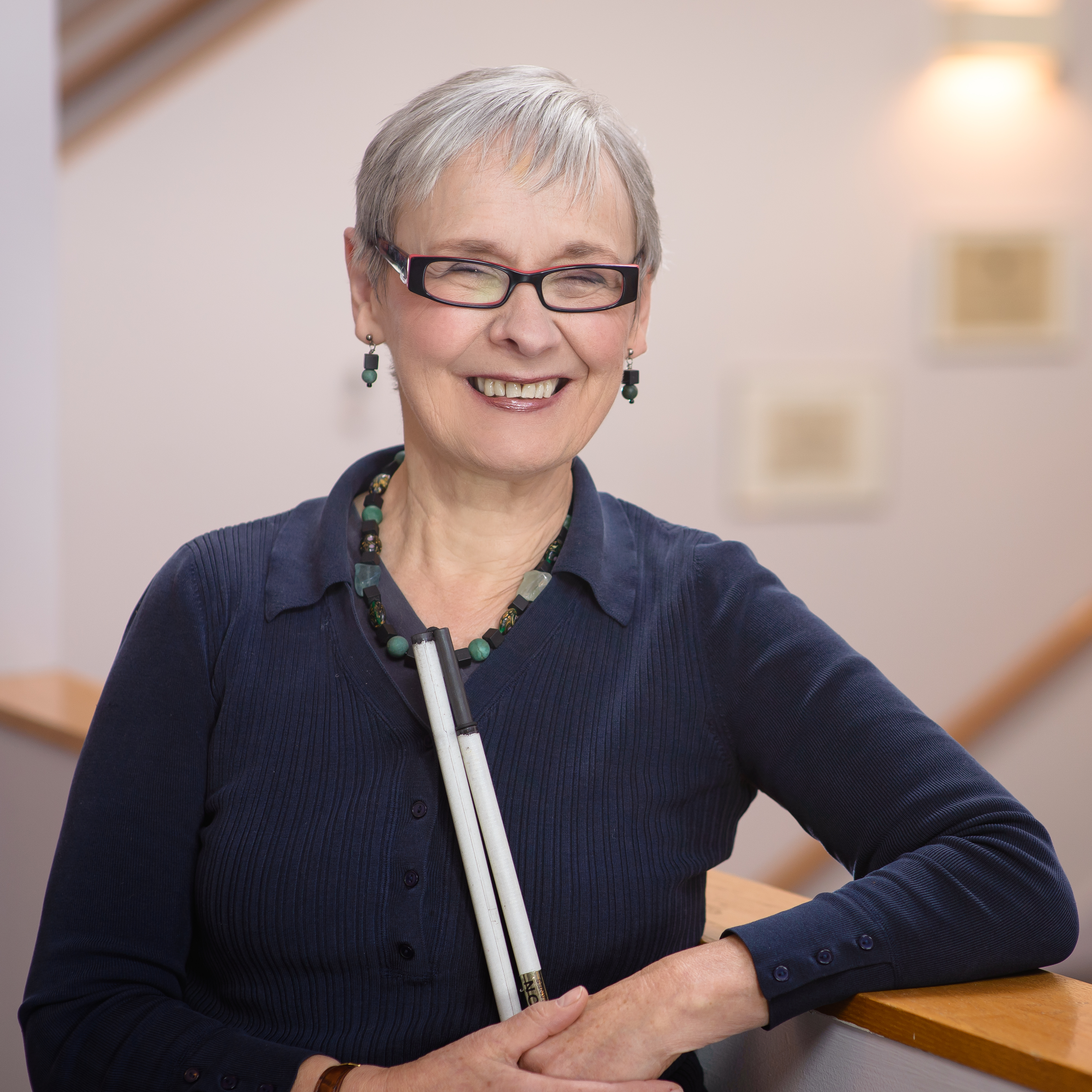Hannah Fairbairn holding a partly folded white cane in one hand and leaning on a stair rail. She has white hair and wears glasses.