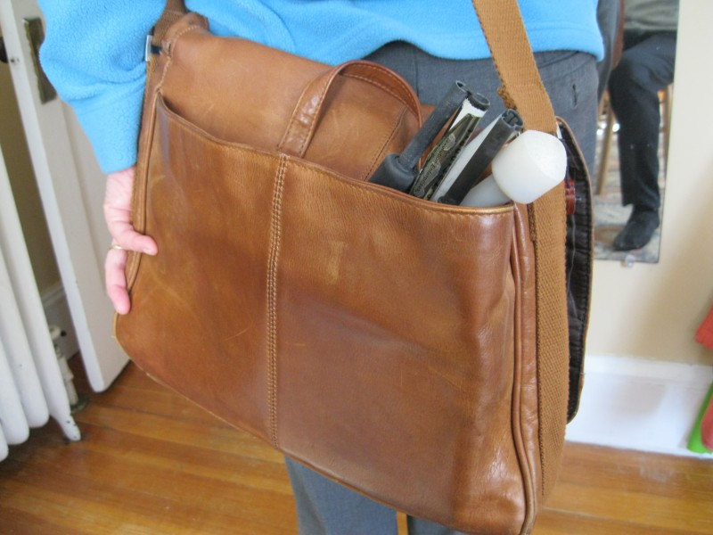 A white cane is stowed at the back of a brown bag with only the tip on view.