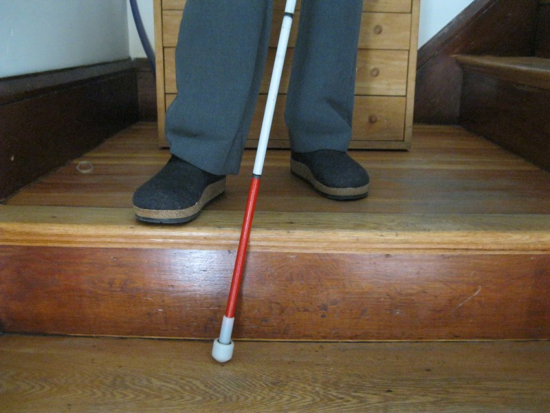The white cane is out of the bag now. It is being used by someone walking downstairs.
