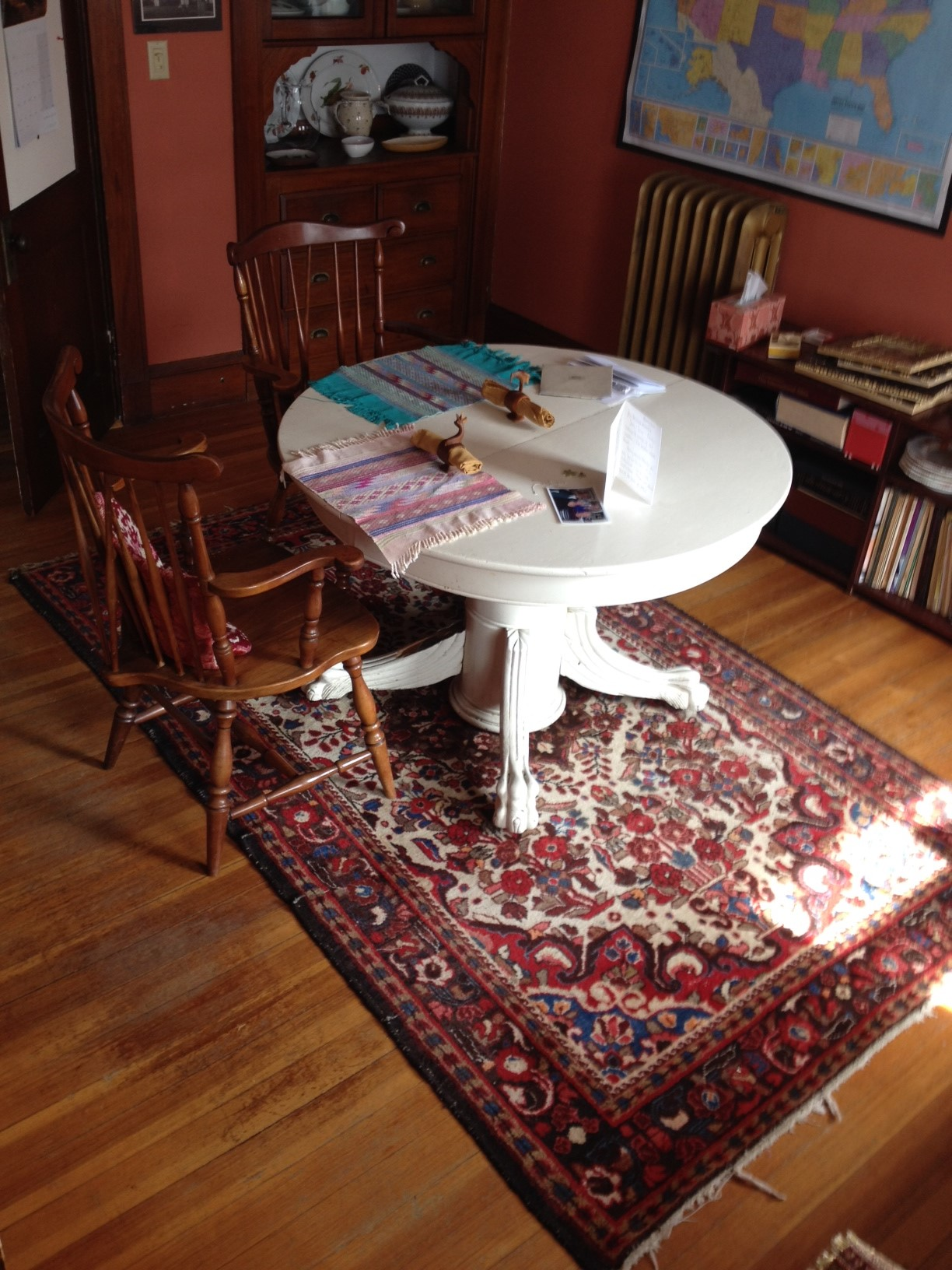 Cream-colored table on dark red rug with two feet of wood floor around the rug to give clear access to the kitchen and hall