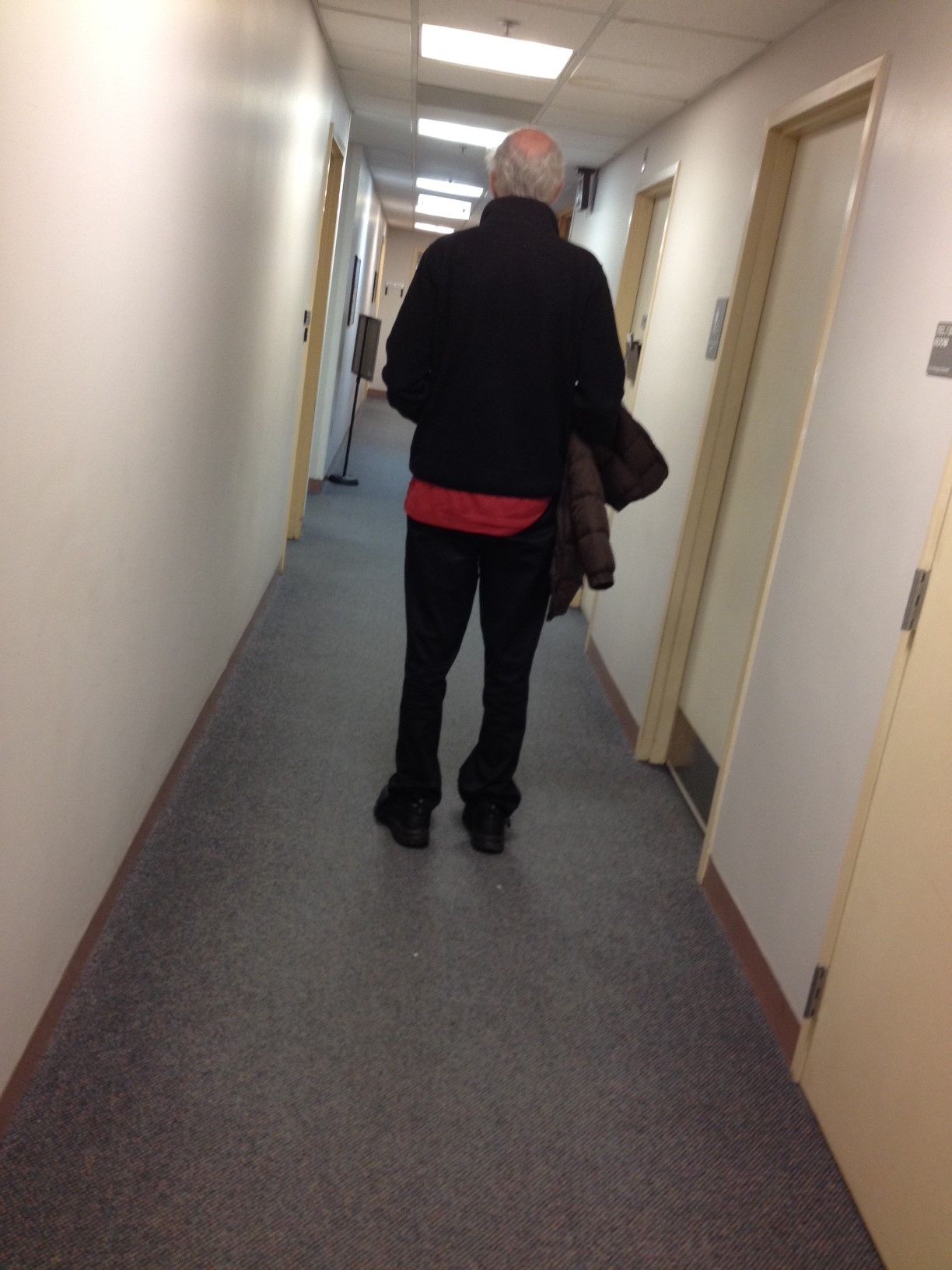 Back view of older man walking down medical hallway with a woman's coat under his arm