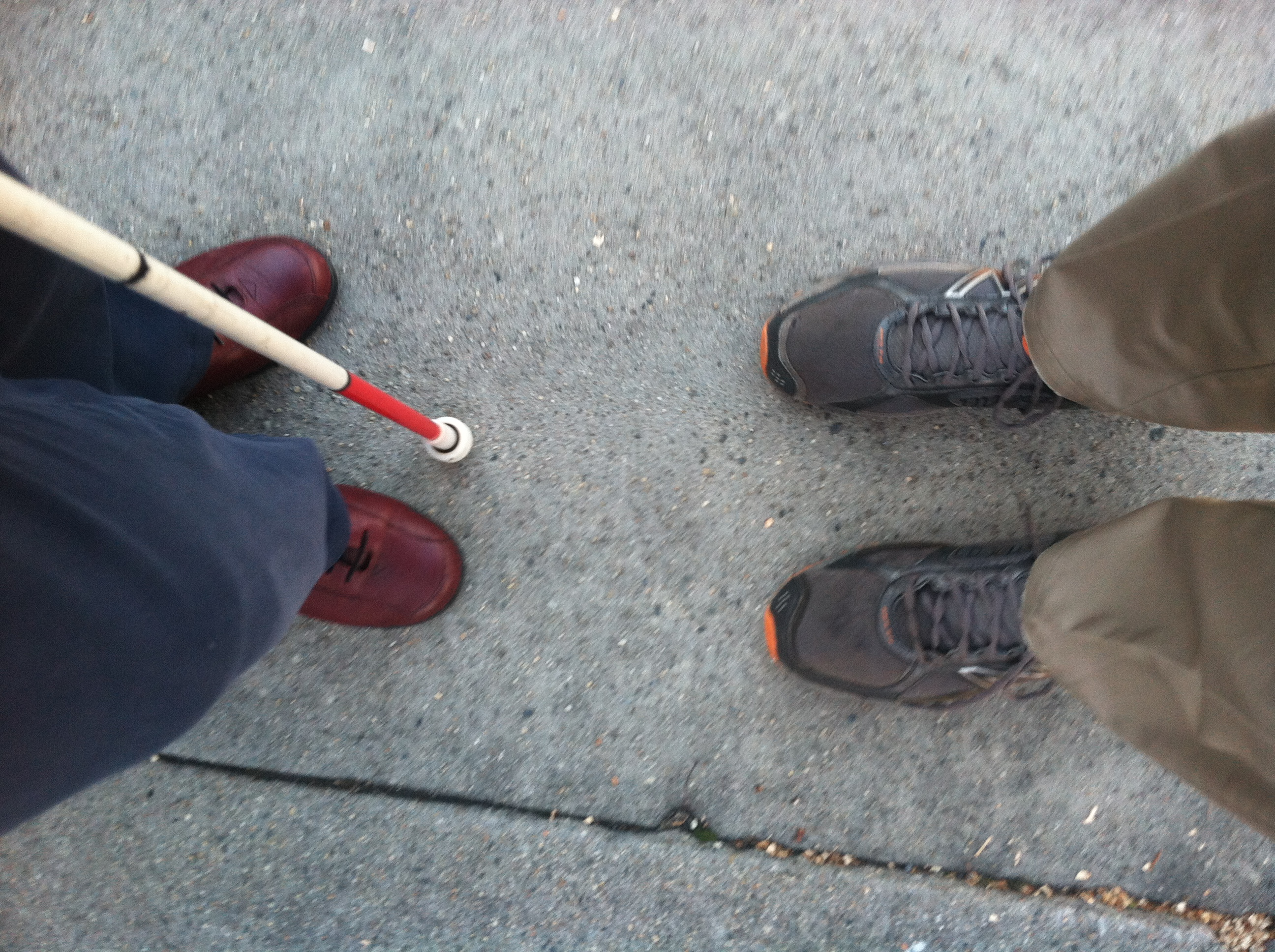 Two pairs of feet meeting on a sidewalk, with a white cane tip in between.