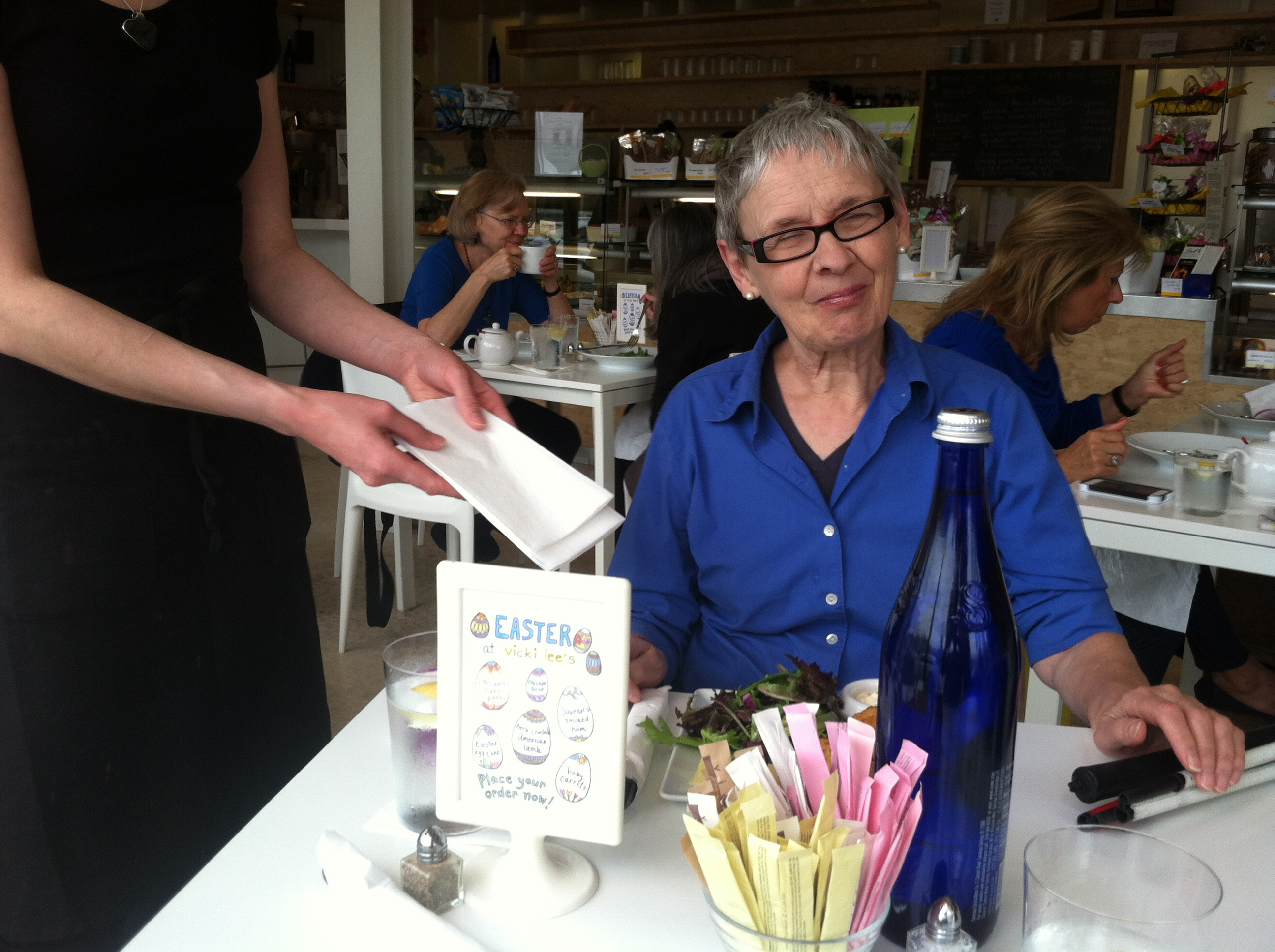 A waitress is holding out a napkin to a woman who seems unaware of it. There is a folded white cane on the edge of the table.