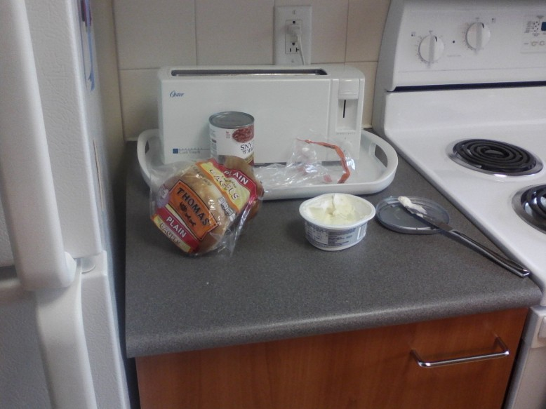 A tub of cream cheese sits open in front of a pop-up toaster with a pack of bagels beside.