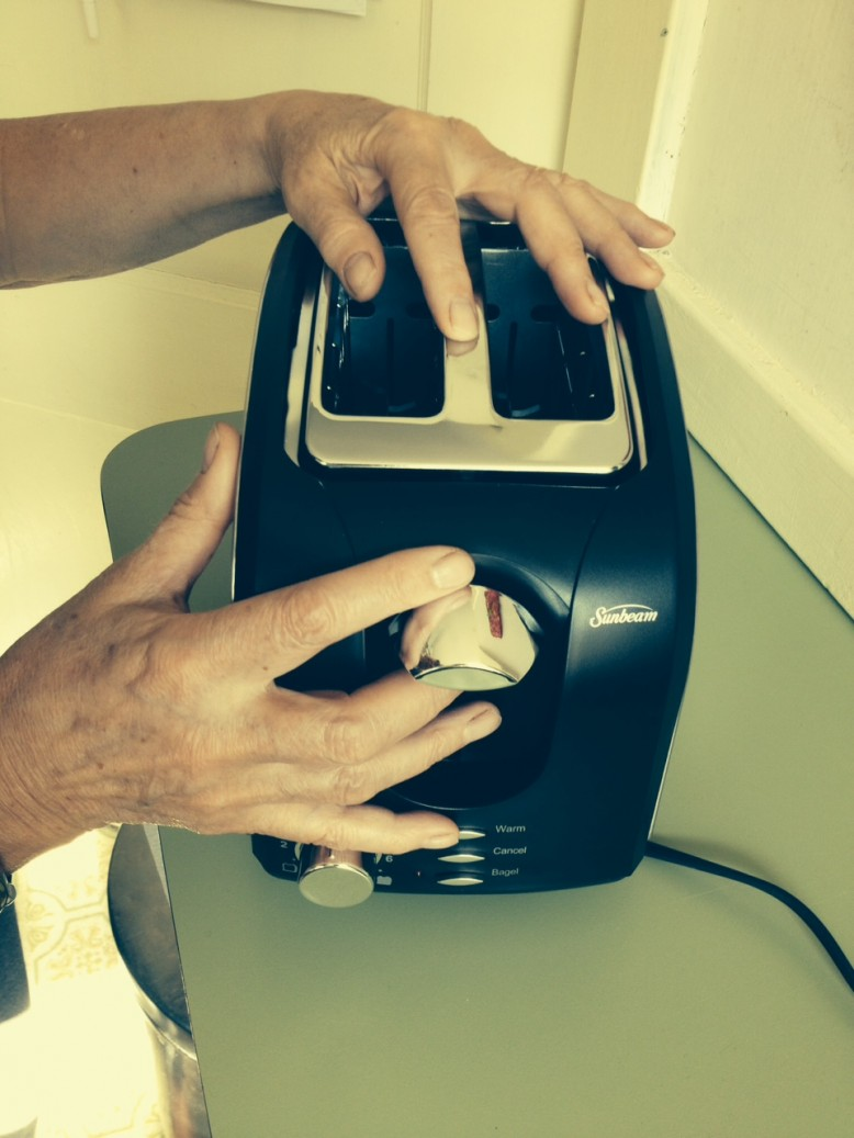 Hands sliding over a new toaster to check out the placement of the slots and controls.