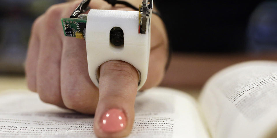 In this Thursday, June 26, 2014 photo, a model wears a FingerReader ring at the Massachusetts Institute of Technology's Media Lab in Cambridge, Mass. Researchers designed and developed the instrument, which enables people with visual disabilities to read text printed on paper or electronic devices. (AP Photo Stephan Savoia)