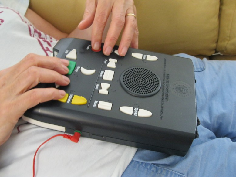 Two hands on a National Library Service for the Blind bookplayer, which is resting on someone's stomach. There is a red ear bud in the earphone jack. .