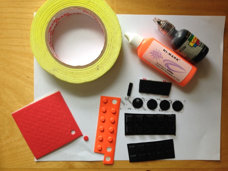 A selection of tactile labels. Waterproof bright lemon tape, Hi Marks tactile paints , Velcro strip and dots , Touch Dots,which are soft, small and good value, flat topped orange bump dots , the classic tactile label, and large and medium black squares.