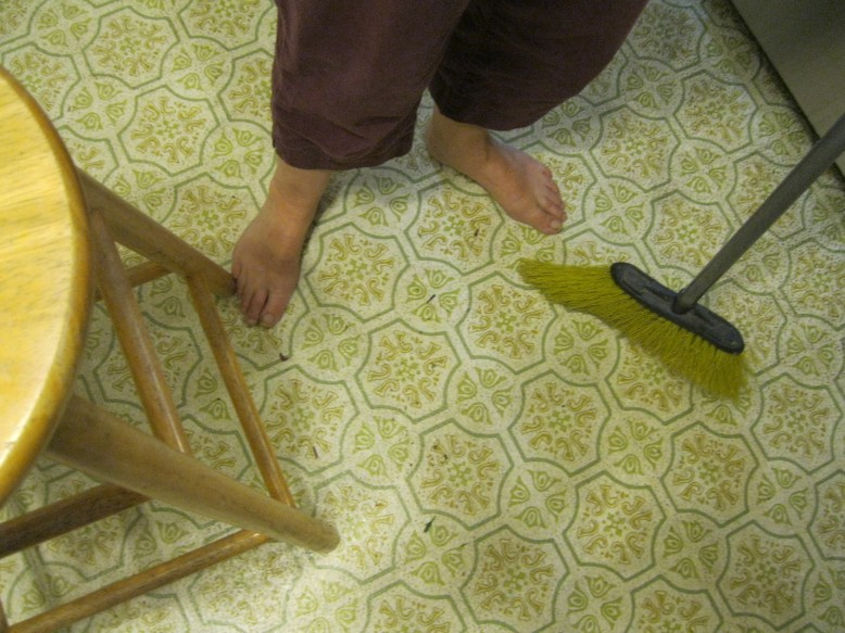 A bar stool on the left is creating a boundary for sweeping or mopping . The broom is sweeping across in front of a pair of feet towards a kitchen cabinets. .