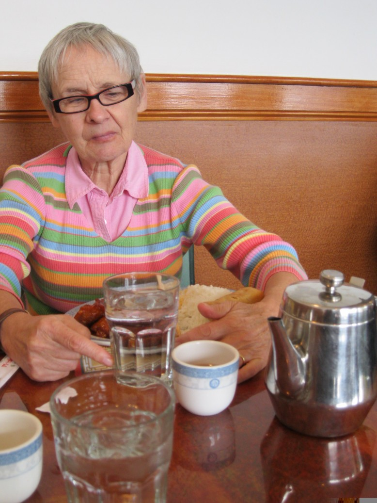 Water glasses and tea bowls sit on a table at a Chinese restaurant. My hands are keeping track of my water glass.