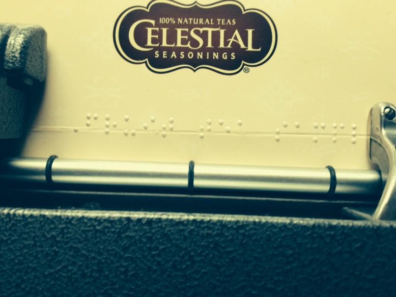 "A brailler is embossing ""fruit tea sampler"" on the cardboard lid of a box of tea.."