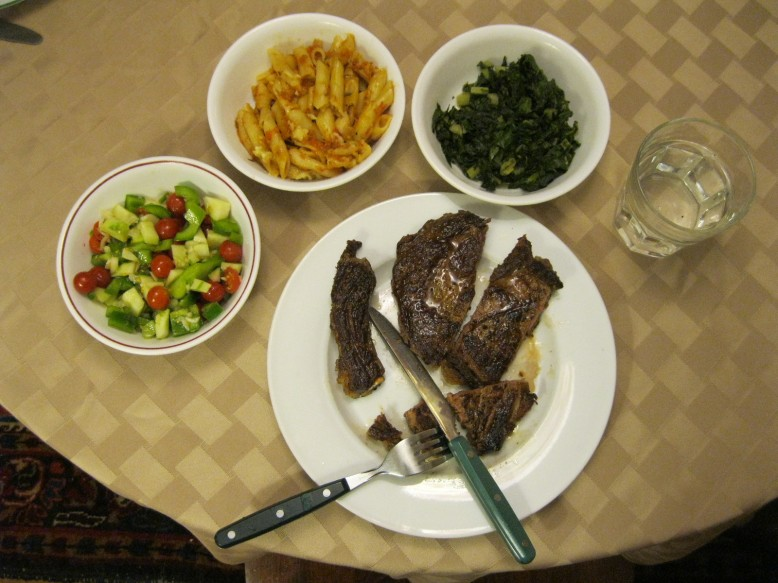 3 small bowls containing left to right chopped salad, short pasta in sauce and spinach, are arranged around a dinner plate containing 3 strips of steak with the bone cut off and set to one side. One strip has a fork stuck into the end of the strip, while a knife cuts across to make a bite-sized piece that the fork can lift straight to your mouth.