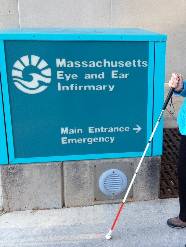 A big blue sign says Massachusetts Eye and Ear Infirmary and a hand holding a white cane shows in front of it.