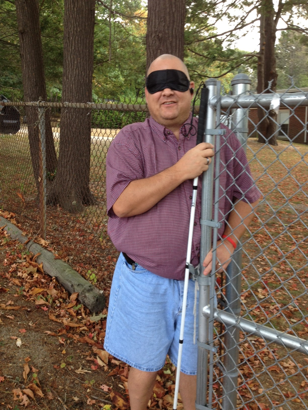 Doug White holds the gate partly open in the fence between the Carroll Center and the neighboring property. We were discussing how to reclaim good boundaries after vision loss. Doug comes from Oklahoma. He is married with 2 teenage sons. [A photo like this was posted on Facebook on Sept. 30 but the post was lost.]