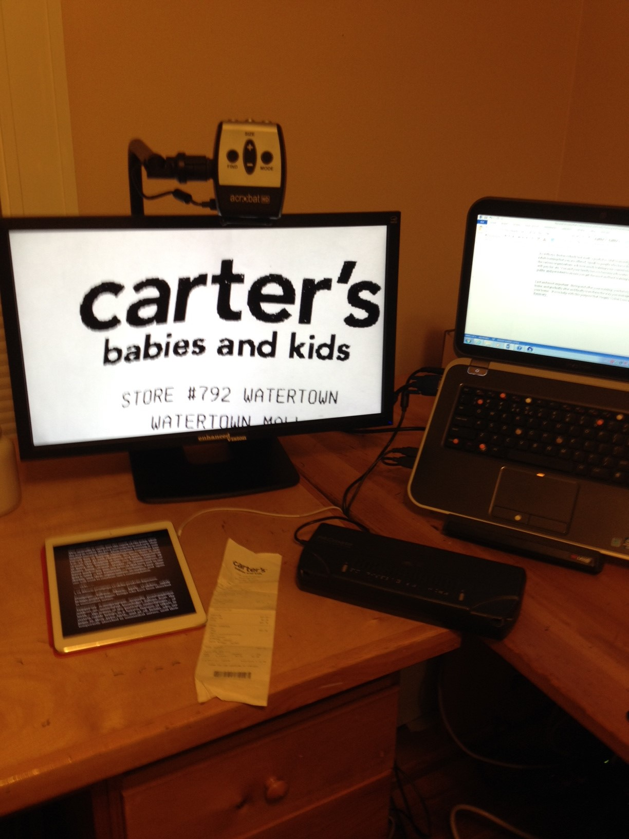 Left to right: iPad showing white text on black background, video magnifier showing enlarged image of store receipt and  refreshable braille displaying text from laptop on right.