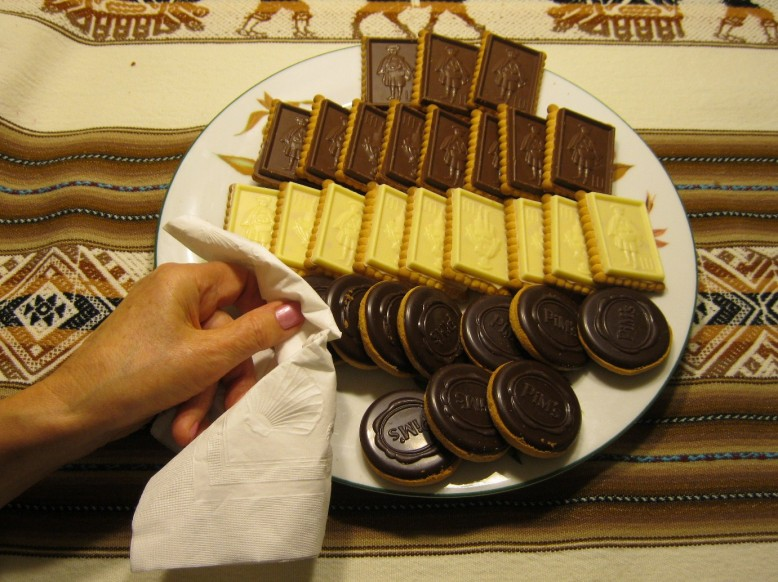 A plateful of chocolate cookies sitting on a striped tablecloth, a hand is picking up a cookie through a white napkin