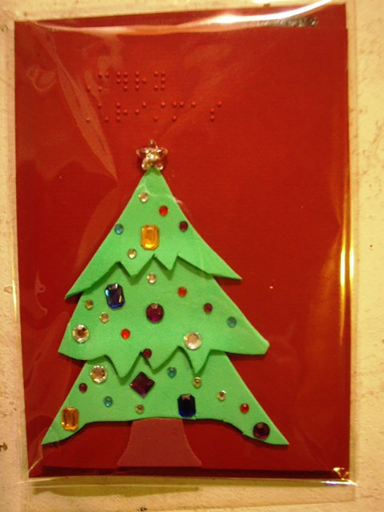 A Christmas tree on a red background from the collection of braille cards by Amber