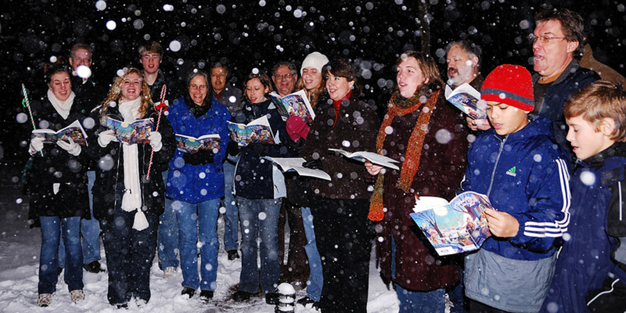 A semi-circle of carol singers standing in the snow  holding their books of carols. .