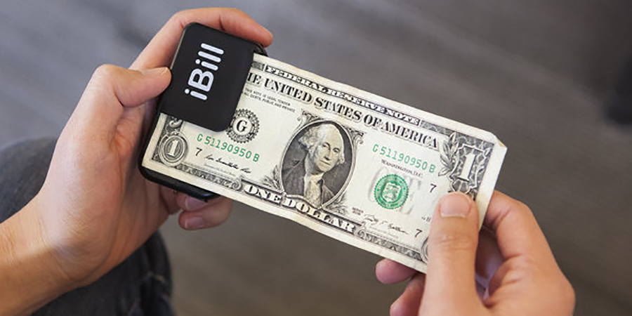 A one dollar  bill is held between two hands with the left hand also holding a small black device with a corner of the bill inserted into it.