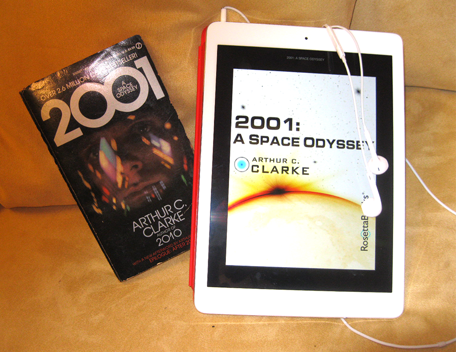 A paperback copy of 2001– a Space Odyssey sits beside an iPad with the same book cover displayed, and an ear bud dangling.