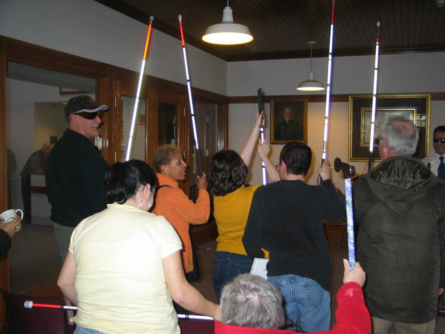 A graduation ceremony at the carroll Center for the Blind - lots of white canes are raised in tribute and triumph.