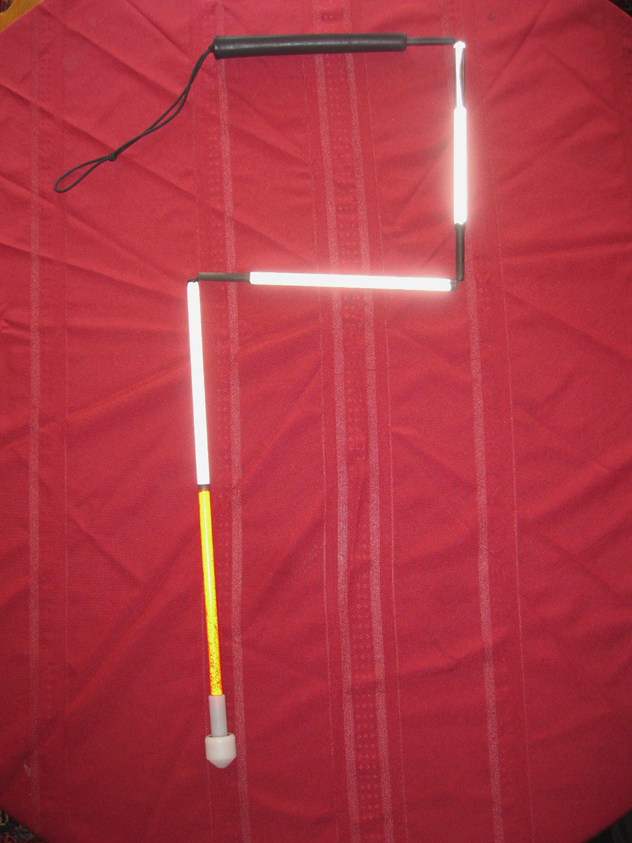 A white cane on a red background. The cane is bent into the shape of a question mark.