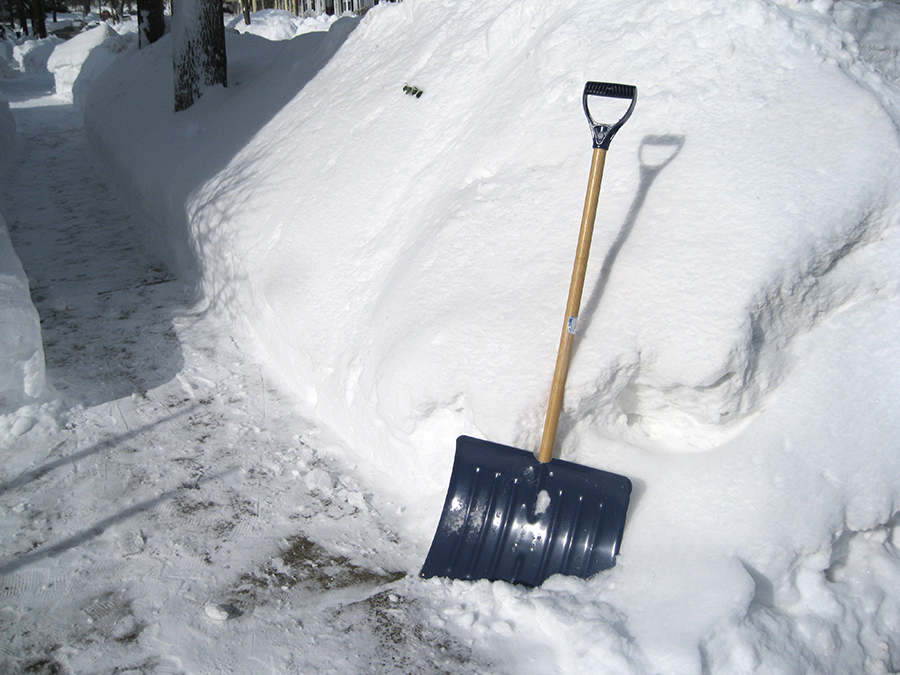 A snow shovel leans against a 6 foot wall of snow, with an icy sidewalk  beside it.