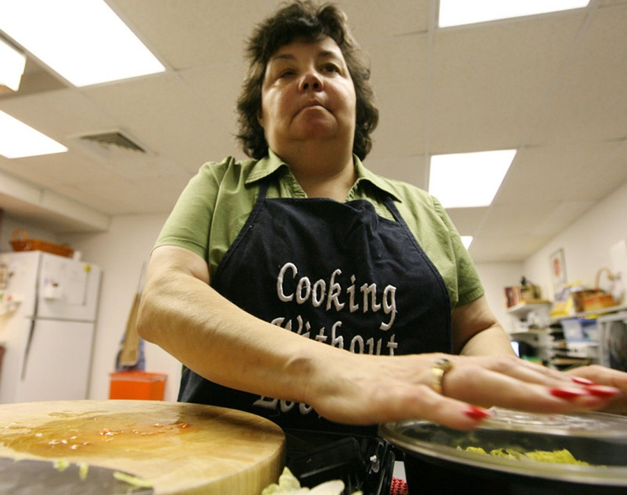 Woman cooking without looking, in Florida program. Photo especially shows her hands working together.