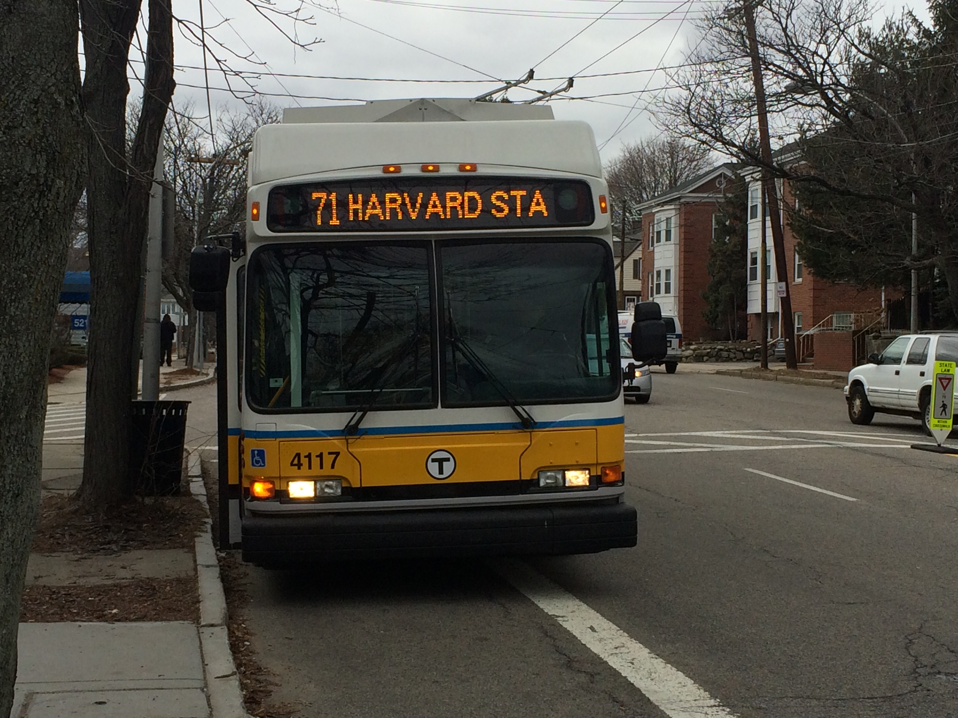 A yellow and white 71 Trolley-bus on its way from Watertown Square to Harvard.