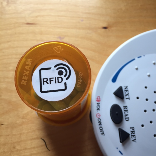 A ScripTalk label, called an RFID label, stuck to the bottom of a pill bottle. To the right there is the white curve and black control buttons on the ScripTalk Patient Station.