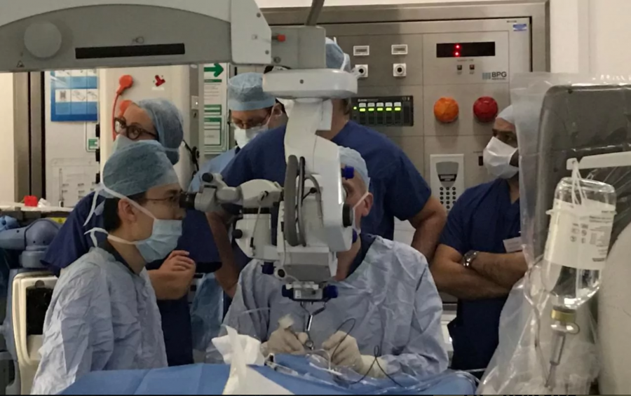 Two doctors look into a mega magnifier as they operate on the patients eye.